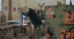 Welder welding metal parts in a workshop - stock footage