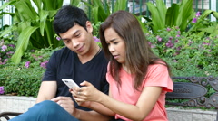 Guy and a girl sitting on a bench at Benjasiri Park watching his phone Stock Footage