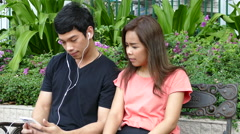 Guy and a girl sitting on a bench at Benjasiri Park listening to music Stock Footage