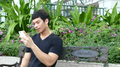 Guy sitting on a bench at Benjasiri Park watching his phone Stock Footage