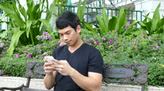 Guy sitting on a bench at Benjasiri Park playing with his phone Stock Footage