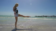 Super slow motion attractive girl kicking ocean water - stock footage