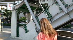 Girl walks at the stairs towards Phrom Phong BTS Station Stock Footage