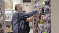 Seller helps the buyer to choose the goods in the shop of accessories Stock Footage