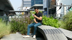 Guy sitting on a bench outside Emporium shopping mall - stock footage