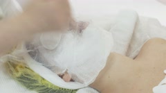 Woman face with clay mask covered by cheesecloth in beauty saloon. Cosmetologist Stock Footage