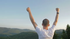 Man On Top Of Mountain With Arms Up - stock footage