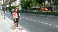 Guy and a girl waiting for a taxi at Sukhumvit road in Bangkok Stock Footage