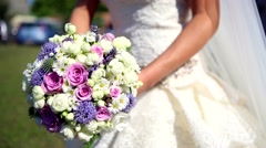 Bride's bouquet and wedding dress in front of the sun. - stock footage