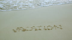 Sand written Vacation washed away by wave Stock Footage