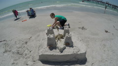 Young boy working on his sand castle creation at ocean beach Stock Footage