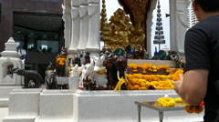 Guy Prays and places flower at Phra Pikanet At Central World Stock Footage