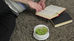 Man laying on a rug reading a book and eating grapes - stock footage