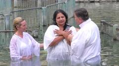 Pilgrims immerse themselves in Biblical Jordan River baptismal site Stock Footage