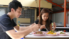 A guy and girl eating som tam, Isan food at Lalai Sap Market in Silom Stock Footage