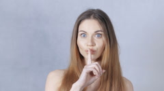 Beautiful woman with bare shoulders making a hushing gesture in studio. - stock footage