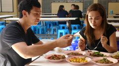 A guy and girl eating som tam, Isan food at Lalai Sap Market in Silom B Stock Footage