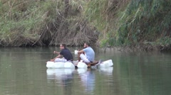 Two guys sail on a boat they made from empty containers - stock footage
