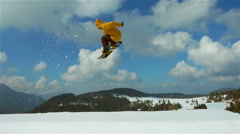 Snowboarder jumping  spinning backside slow motion Stock Footage