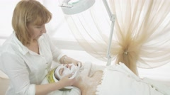 Stock Video Footage of Adult cosmetologist rub clay in adult woman face in beauty saloon. Moisten mask