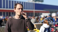 Man smoking electronic cigarette in public city place slow motion Stock Footage