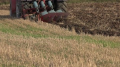 agricultural machine tractor plough turn up field soil in autumn. 4K - stock footage