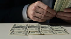 Close-Up of a Businessman Lays Out Hundred Dollar Bills on the Table Stock Footage