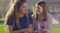 Teen Girls Share Headphones And Bob Their Heads Along To Music On Smartphone Stock Footage