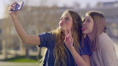 Teens Take Selfies Together On City Park Bench, They Make Funny Faces - stock footage
