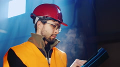 Worker in overalls and a helmet uses a tablet Stock Footage