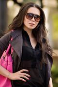 Beautiful latinonos woman wearing sunglasses, casual wear and handbag walking - stock photo