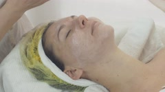 Stock Video Footage of Cosmetologist rub moisturizing cream in woman face in beauty saloon. Skincare