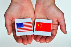 Two hands holds the national flags of the United States of America (L) and of Stock Photos