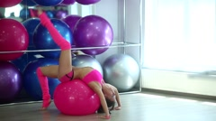 Girl with thin waist smiling and doing fitness on the ball Stock Footage