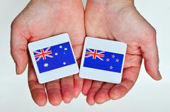 Two hands holds the national flags of Australia (R) and New Zealand (L) Stock Photos