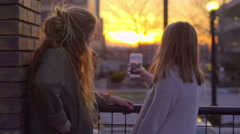 Teen Takes Video Of Sunset In City, On Her Smartphone, Her Friend Points To View Stock Footage
