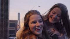 Teens Watch Sunset, Turn Around, Girl Jumps On Her Friend For A Piggyback Ride Stock Footage