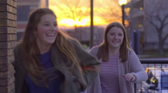 Teens Watch Sun Go Down Over City, Then Turn And Run Toward Camera - stock footage