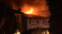 House Fire With Flames Through Roof Stock Footage