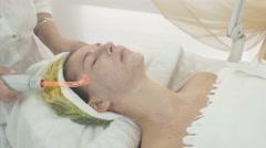 Cosmetologist use darsonval on woman face in beauty saloon. Moiston cream Stock Footage