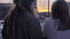 Teen Girls Lean Against Railing And Watch Sunset In The City Stock Footage