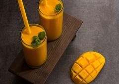 Mango Lassi  Indian Mango Juice with Yogurt with sliced mango on the side - stock photo