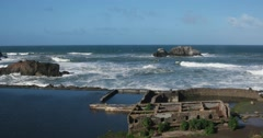 Moderate size surf breaking along the sea wall at Sutro Baths in San Francisco.  - stock footage