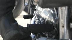 A Man's Leg Trying to Start a Black Motorcycle. Stock Footage