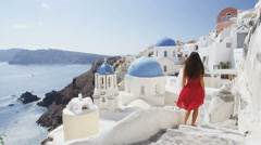 Elegant Woman Walking Down Stairs In Oia Santorini - traveler at landmark Stock Footage
