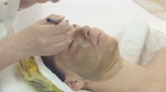 Cosmetologist put mask from green clay on woman face by brush in beauty saloon - stock footage