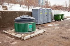 Public toilets and garbage cans on city street Stock Photos
