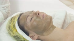 Woman face with green clay cosmetic mask in beauty saloon. Skincare. Cosmetology - stock footage