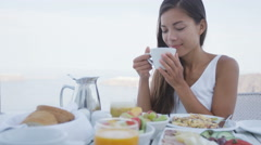 Woman Drinking Morning Coffee At Breakfast Table Outdoors in Summer Stock Footage