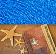 Photo album with starfish on a background of blue water. - stock photo